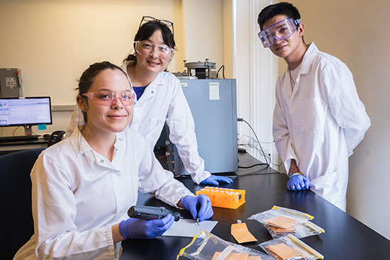 Professor Kim and two undergraduate students occupy her lab.